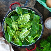 Fresh Baby Spinach Leaves In A Bowl And Eggs On A Wooden Table.