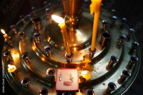 baptismal cross and pendant of angels on the candlestick in the church Fototapeta