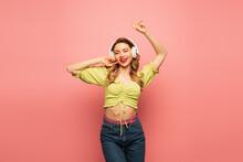 Joyful Woman In Wireless Headphones Dancing On Pink