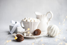 Cup Of Miniature Marshmallows Next To A Christmas Gift, Decorations And String Lights