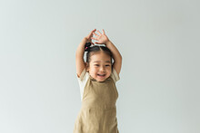 Happy Asian Toddler Girl With Raised Hands Isolated On Grey