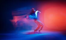 Dancing Female Standing On Tiptoe In Colourful Neon Studio Light. Long Exposure. Contemporary Hip Hop Dance
