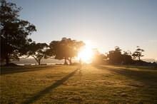 Cyclist Walking Bike Across The Sunrise At A Park