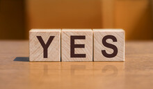 YES Text On Wooden Cubes On Orange Wall Background.