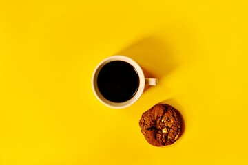 white cup of black coffee and cookie with pieces of chocolate on a yellow background