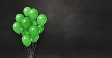 Green Balloons Bunch On A Black Wall Background. Horizontal Banner.