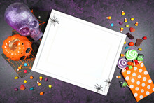 Halloween Theme White Wood Wall Art Frame Mockup Flatlay On Textured Purple Background With Purple And Orange Skull, Pumpkin And Trick Or Treat Candy. Product Mock Up With Negative Copy Space.