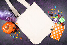 Halloween Theme Tote Bag Mockup Flatlay On Textured Purple Background With Purple And Orange Skull, Pumpkin And Trick Or Treat Candy. Product Mock Up With Negative Copy Space.