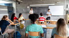 Teen Asian Boy High School Student Giving A Presentation In Class To His Multiracial Classmates And Teacher. Horizontal Banner Image.