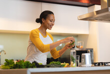 Smiling Mixed Race Woman In Kitchen Preparing Health Drink