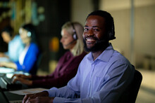 Portrait Of African American Businessman Working At Night Wearing Headset