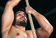 Muscular Man Climbing Rope In Gym