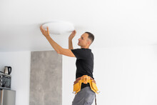 Worker Installing Lamp On Stretch Ceiling Indoors. Space For Text