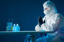 Man In Face Shield And PPE Crossed His Arms. Employee Of Viral Lab Prays Before Work. He Creates A Vaccine Against Virus. Virologist Praying God For A Vaccine. Doctor Praying During A Pandemic