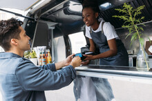 Young Man With Credit Card Paying To A Saleswoman At A Food Truck. Female Entrepreneur In Apron Receiving Payment From A Customer.