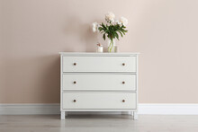 White Chest Of Drawers With Bouquet And Candle Near Beige Wall