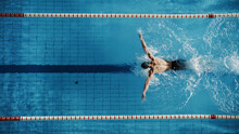 Aerial Top View Male Swimmer Swimming In Swimming Pool. Professional Determined Athlete Training For The Championship, Using Butterfly Technique. Top View Shot