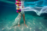Underwater bride with flowers in a white dress in dark blue water, mediterranean sea