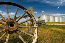 A Vintage Horse Drawn Cart Wheel And Grain Silos On The Canadian Prairies During A Summer Day.