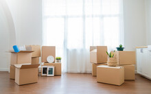 Moving In. Stack Of Cardboard Boxes And Household Stuff Belongings In The White Empty Apartment Room Carton With Copy Space. Lifestyle Moving House Relocation Unpacking Background Concept Banner