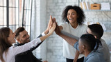 Overjoyed young multiracial businesspeople join hands give high five celebrate shared victory or win in office. Smiling millennial diverse employees engaged in teambuilding activity. Success concept.
