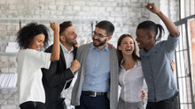 Overjoyed Young Multiethnic Businesspeople Have Fun Celebrate Shared Business Success Or Victory In Office. Smiling Multiracial Diverse Employees Feel Excited Win Get Good Results. Teamwork Concept.