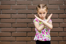 A Little Girl Shows A Stop Gesture With Her Arms Crossed In Front Of Her. A Child With Braided Hair And A Bright T-shirt Against A Brick Wall Is Very Serious And Shows A Sign Enough