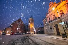 Poland, Subcarpathia, Rzeszow, Illuminated Street With Church In Winter Snowfall At Night