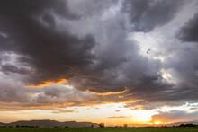 Usa, Idaho, Bellevue, Storm Clouds Over Fields At Sunset