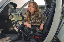 Dreamy Tween Girl Sitting In Open Cockpit Of Helicopter