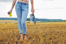 Barefoot Girl With Sneakers And Cardboard Cup With Coffee In Hand Stand In The Agricultural Field