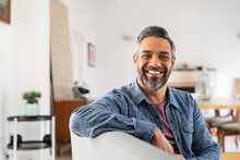 Happy Mature Indian Man Smiling At Home