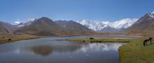 High Altitude Landscape Panorama Of Snow Capped Lenin Peak Near Achik Tash Base Camp With Lake And Reflection, Trans-Alai Mountain Range, Kyrgyzstan