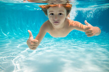 Child Swims Underwater In Swimming Pool, Happy Active Boy Dives And Has Fun Under Water, Kids Watersport. Children Play In Tropical Resort. Family Beach Vacation And Summer Activity.