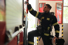 Firefighter In Uniform Opening Door Of Fire Truck At Station
