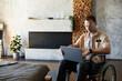 Leinwandbild Motiv Portrait of modern adult man in wheelchair using laptop at home in designer interior, copy space
