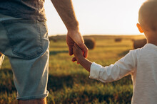 Father's And His Son Holding Hands At Sunset Field. Dad Leading Son Over Summer Nature Outdoor. Family, Trust, Protecting, Care, Parenting Concept