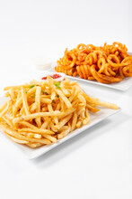 A View Of A Plate Of French Fries And A Plate Of Curly Fries.