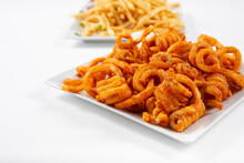 A View Of A Plate Of Curly Fires, And A Plate Of Common French Fries In The Background.