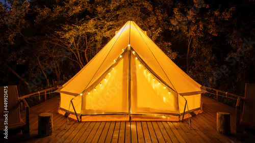 Glamping at night, glowing tent with chairs in front of it