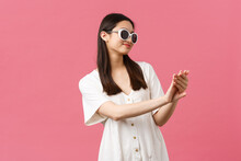 Beauty, People Emotions And Summer Leisure And Vacation Concept. Smiling Good-looking Asian Glamour Girl Looking At Her Manicure Pleased After Visiting Nail Studio, Standing Over Pink Background