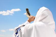 Jewish Man In Tallit Blowing Shofar Outdoors. Rosh Hashanah Celebration
