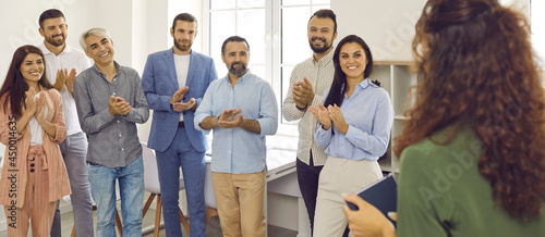 Fotografia Positive male and female audience standing in office applauding speaker, lecturer, coworker, executive manager or business team trainer for presentation