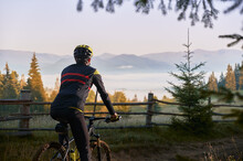 Cropped Back View Of Male Cyclist In Cycling Suit Riding Bike With Hills On Background. Man Bicyclist Wearing Safety Helmet While Enjoying Bicycle Ride In Mountains. Concept Of Active Leisure.