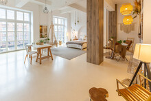 Fashionable Modern Interior Of A Light Studio Apartment With Wooden Columns In The Loft Style, Decorated With Brick, Marble And Wood With Stylish Furniture And White Walls