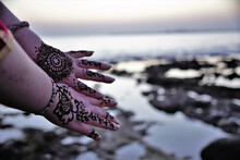 Female Presenting Her Hands With Indian Henna Over A Sunset Beach Background