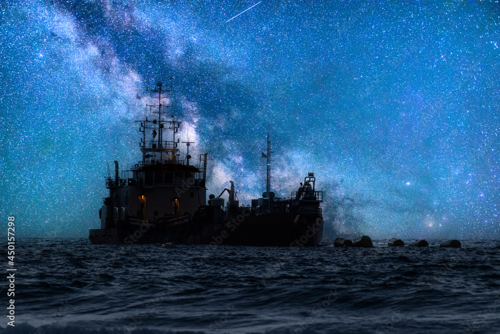 ship in the sea at night and the milkyway