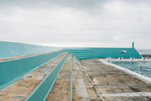 Horizontal Shot Of A Concrete Ocean Pool Bleacher With A Person Swimming On A Cloudy Day