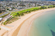 Aerial View Of A Curved Sandy Beach In Front Of A Grassy Reserve And City In The Background