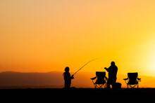 Silhouettes Of People Fishing On The Beach At Sunset